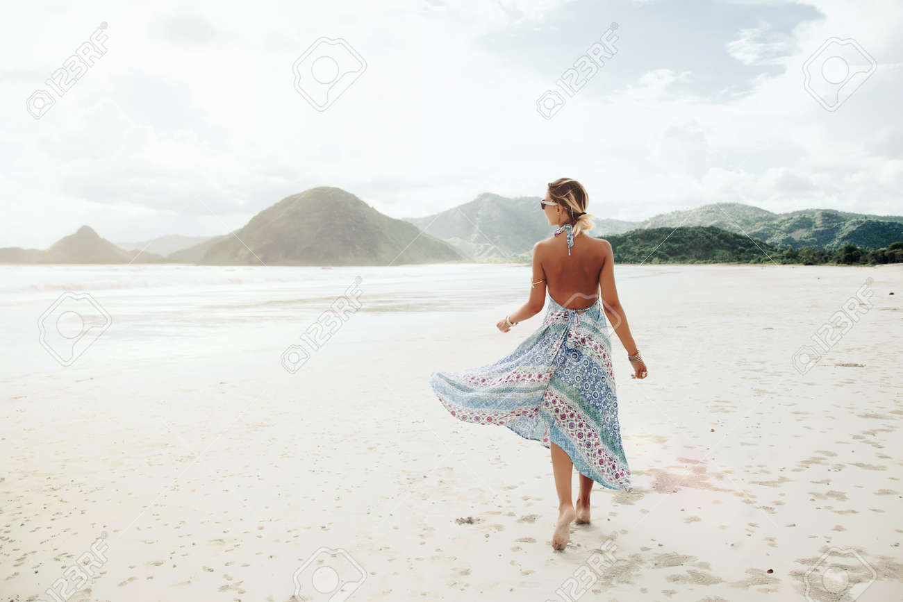 Woman wearing ethnic flying dress walking barefoot at the beach, Lombok, Indonesia - 55493184