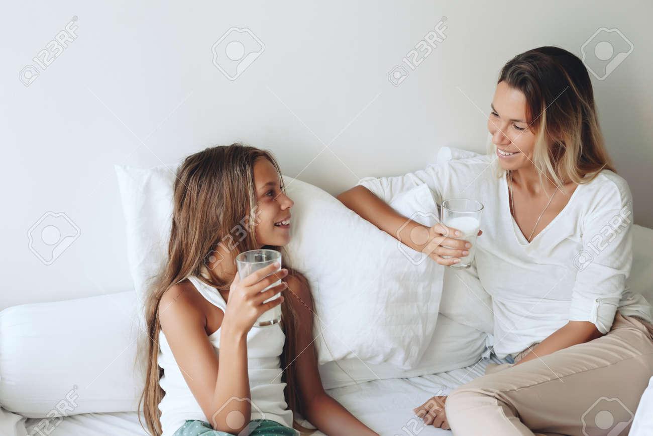 mom with her tween daughter relaxing in bed, positive feelings
