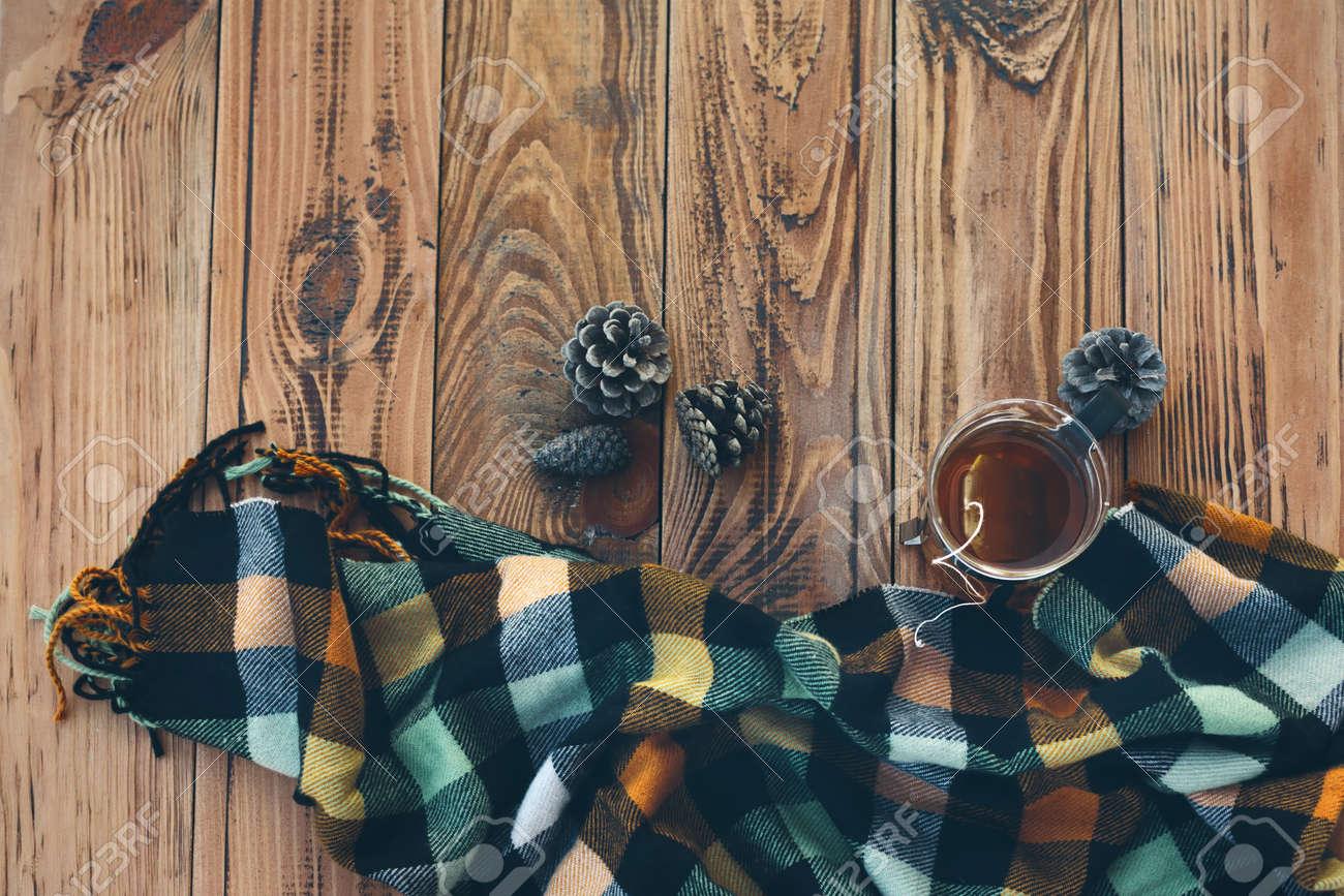 488795d28161 Banque d images - Mug avec sachet de thé et écharpe d hiver à carreaux sur  la table en bois vintage, vue de dessus