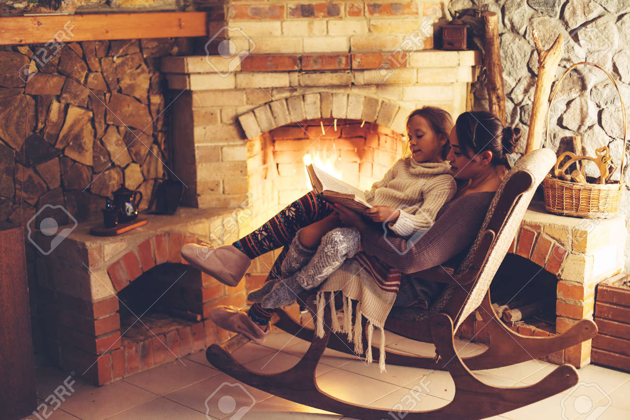 Mom with child reading book and relaxing by the fire place some cold evening, winter weekends, cozy scene - 63235571