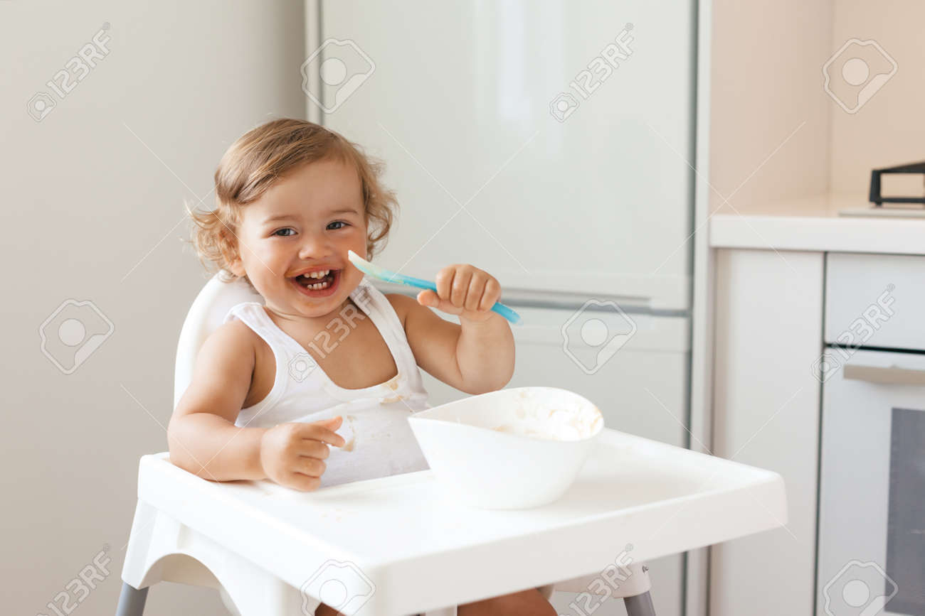 Cute baby 1,4 years old sitting on high children chair and eating vegetable alone in white kitchen - 63235682