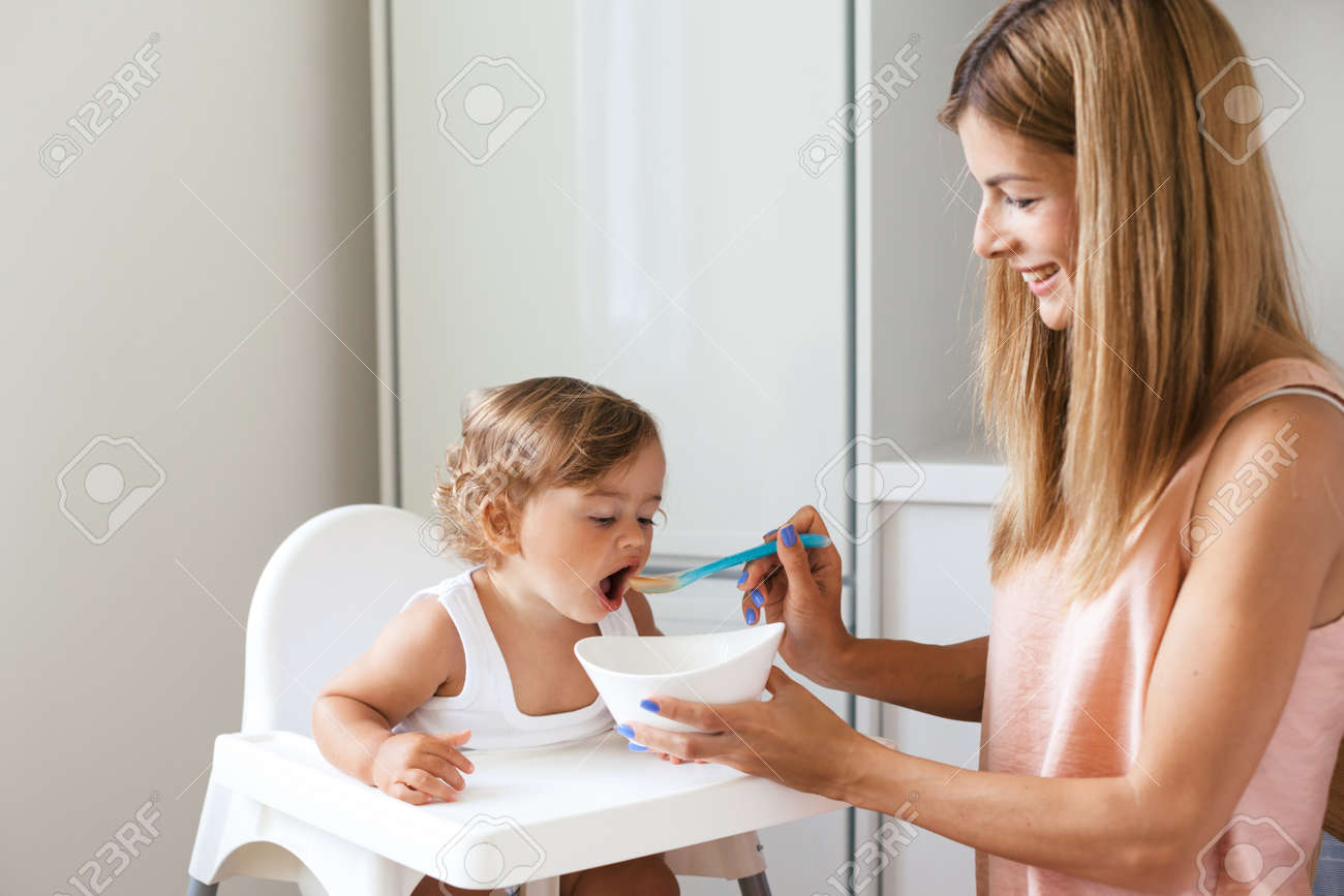 Mom Feeding Baby With Spoon Of 1,4 Years Old In White Kitchen Stock ...