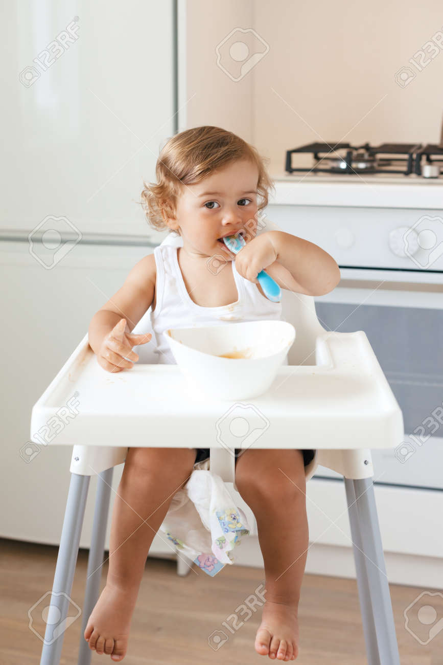 Cute baby 14 years old sitting on high children chair and eating vegetable alone  sc 1 st  123RF.com & Cute Baby 14 Years Old Sitting On High Children Chair And Eating ...