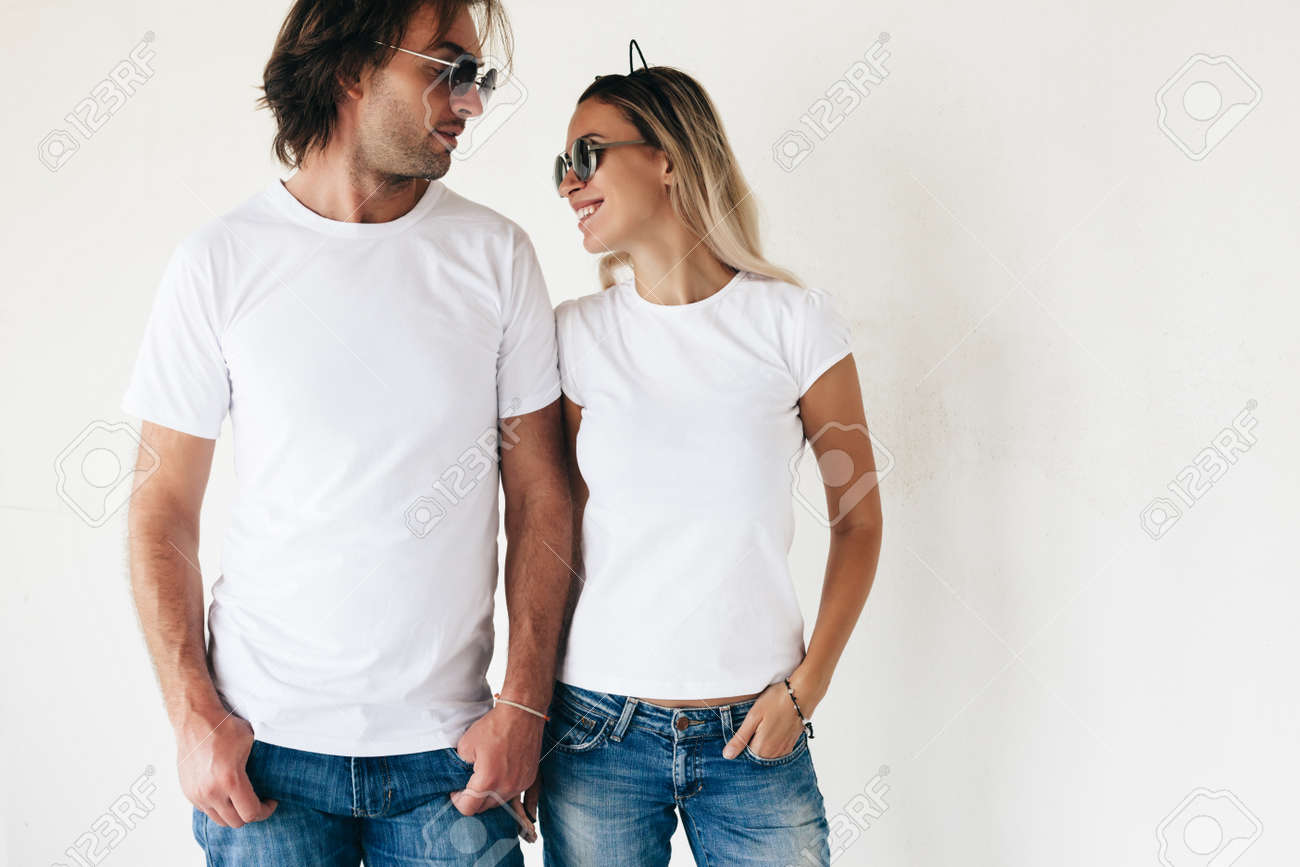 Two hipster models man and woman wearing blanc t-shirt, jeans and sunglasses posing against white wall, toned photo, front tshirt mockup for couple - 63235766