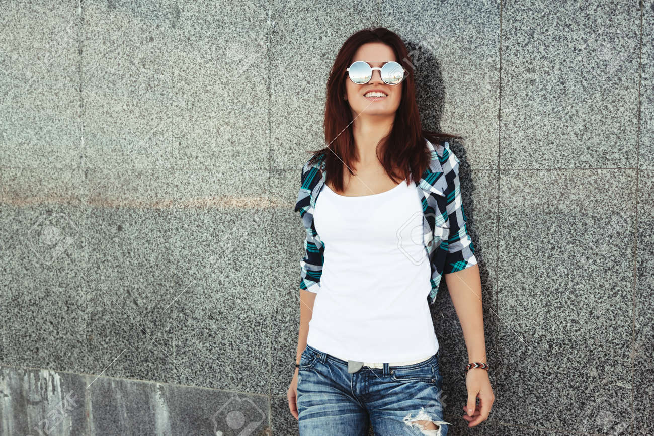 81d1ccb877 Hipster girl wearing white t-shirt and fashion sunglasses posing against  wall
