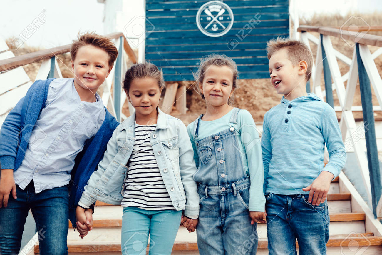 Group of fashion children wearing denim clothing having fun on the sea shore. Autumn casual outfit in blue and navy color. 7-8 years old models. - 63833742