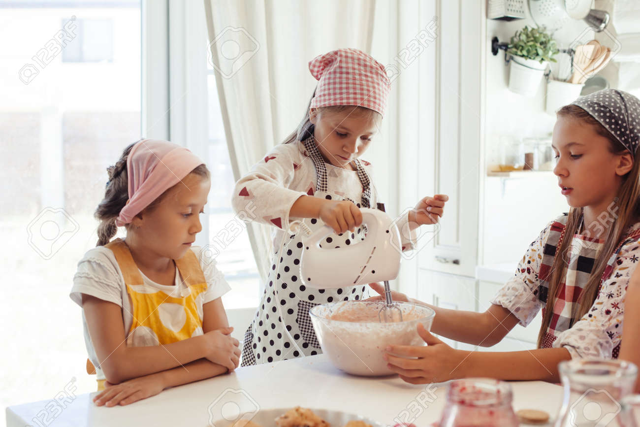 Group Of Children Cooking In The White Kitchen. Kids Wearing.. Stock ...