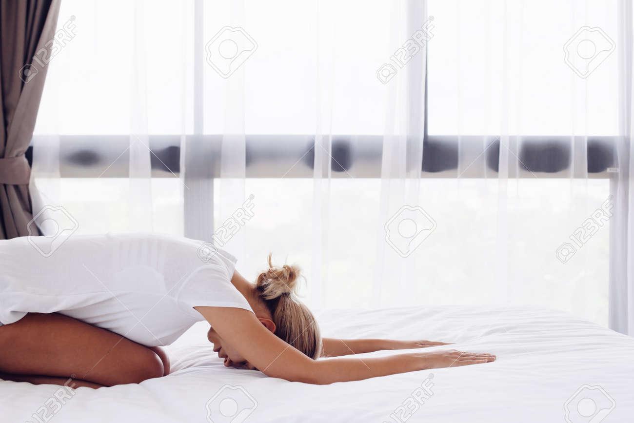 donna che fa esercitazione di yoga sul letto a casa. allenamento ... - Camera Da Letto Donna
