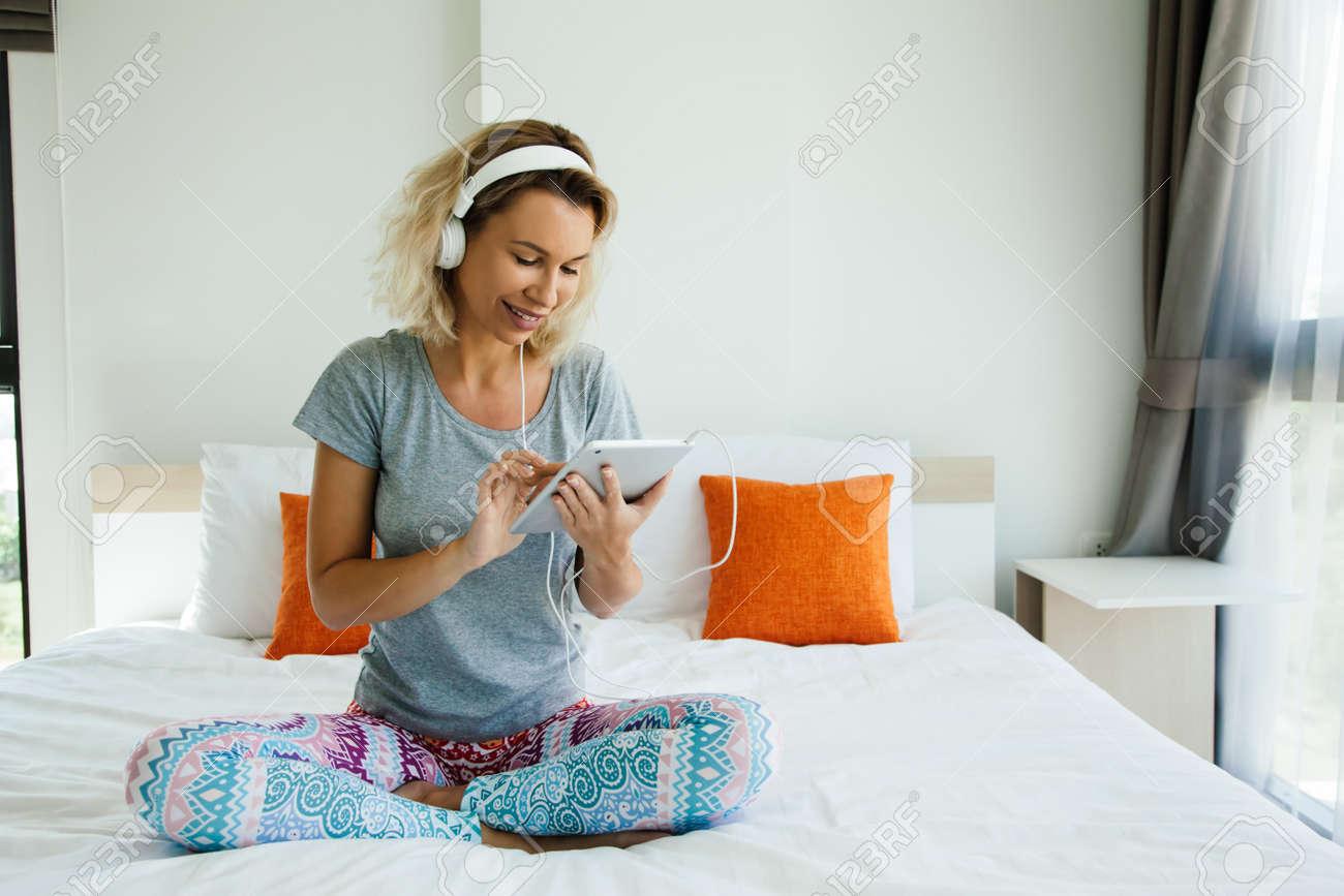 Youn donna in cuffie è agghiacciante e ascoltare musica utilizzando tablet  pc sul letto in camera da letto a casa