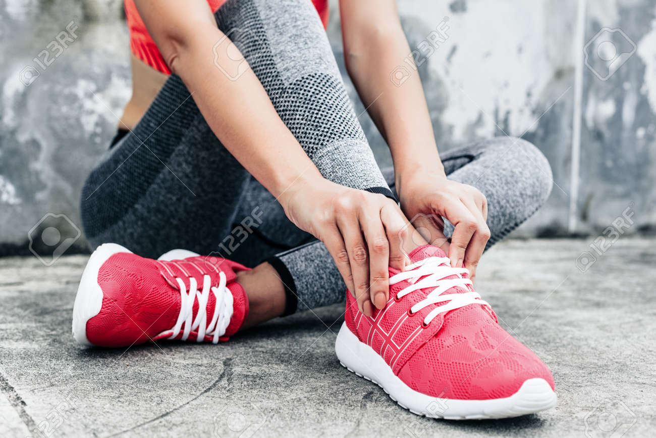 Fitness sport woman in fashion sportswear doing yoga fitness exercise in the city street over gray concrete background. Outdoor sports clothing and shoes, urban style. Tie sneakers. - 69545862