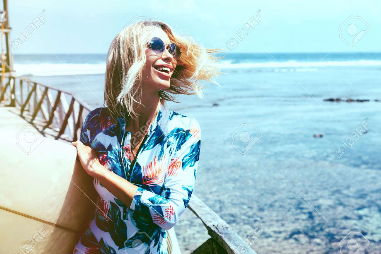 Surfer Mädchen im Sport Badebekleidung und Sonnenbrillen mit Surfbrett auf dem Strand aufwirft. Aktiver Lebensstil und Sommerferien. Standard-Bild - 70918745