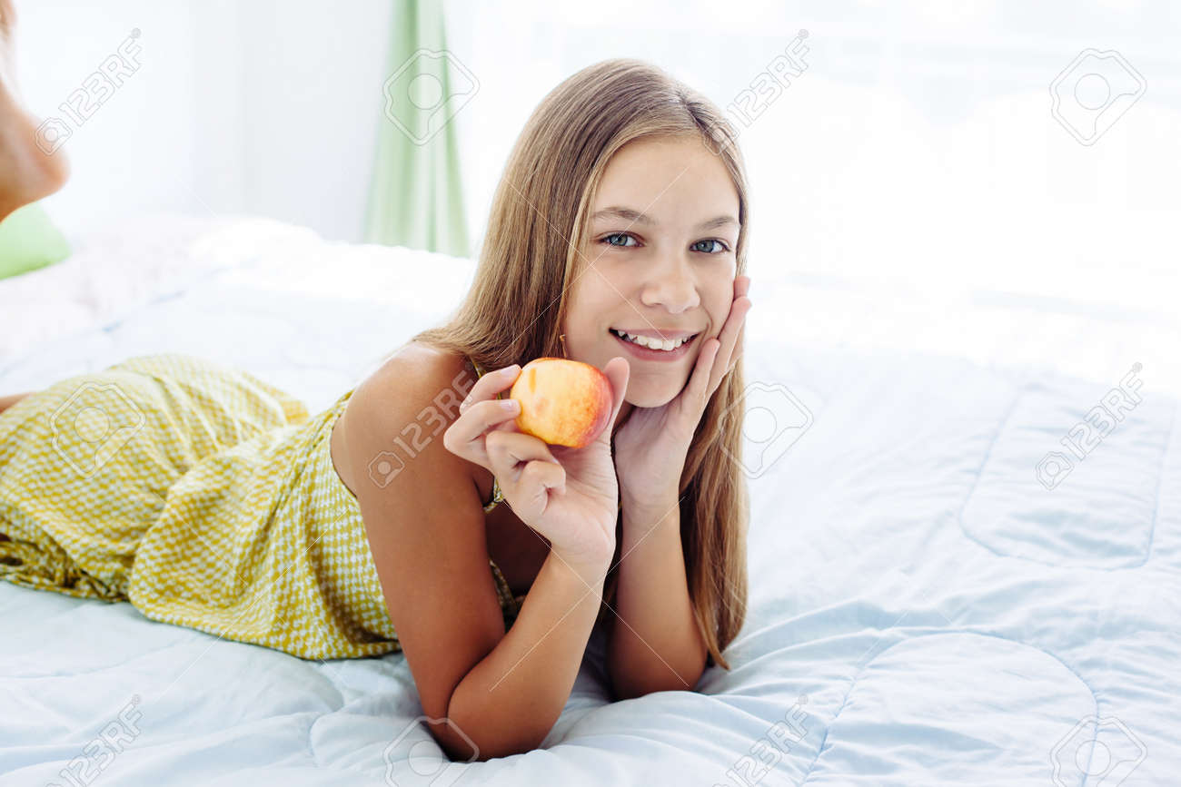 10 years old pre teen girl eating apple while relaxing in bedroom. Healthy  food for