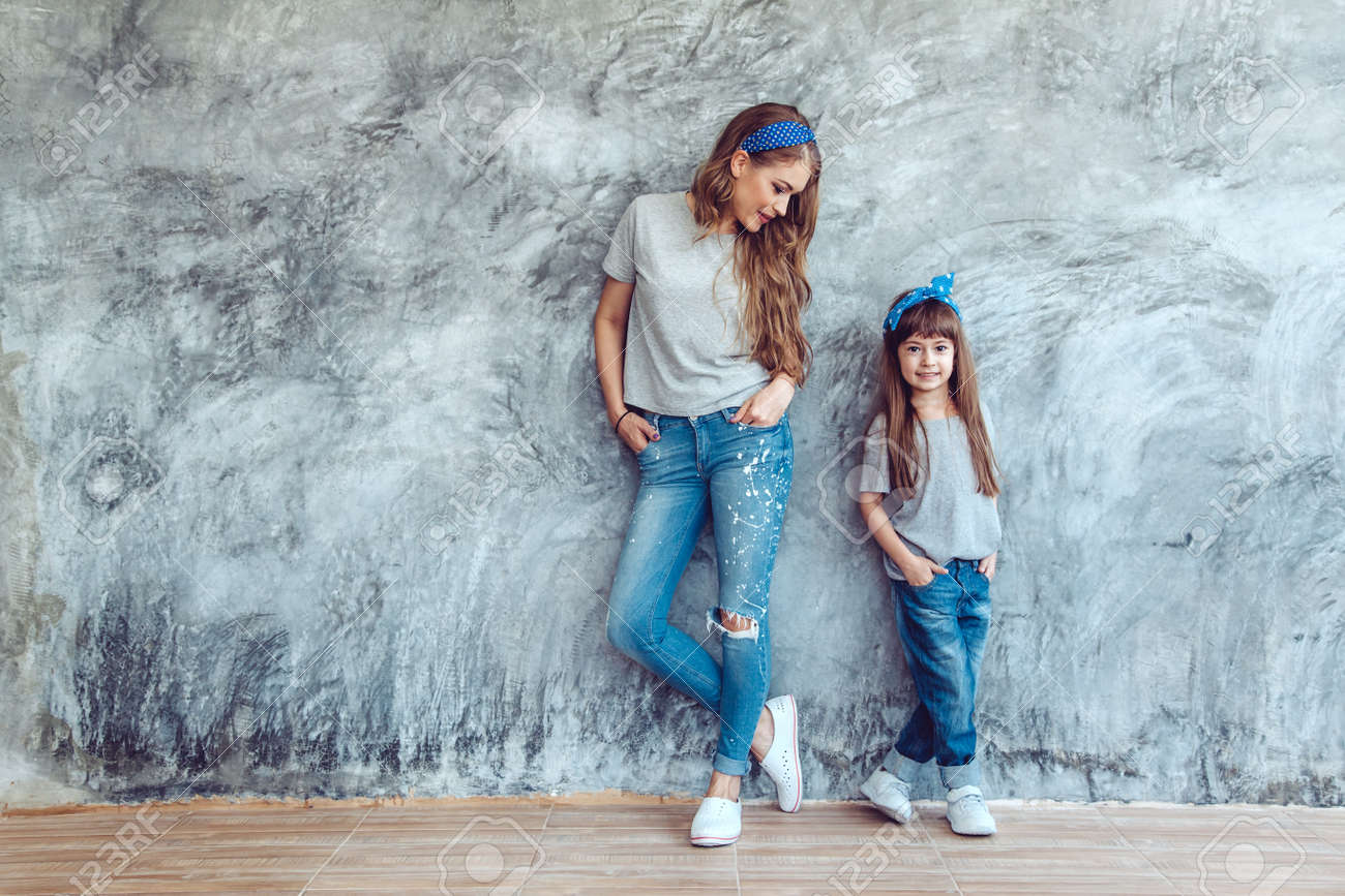 Young beautiful mom with her daughter wearing blank gray t-shirt and jeans posing against rough concgrete wall, minimalist street fashion style, family same look, clothing for parent and child. - 73348887