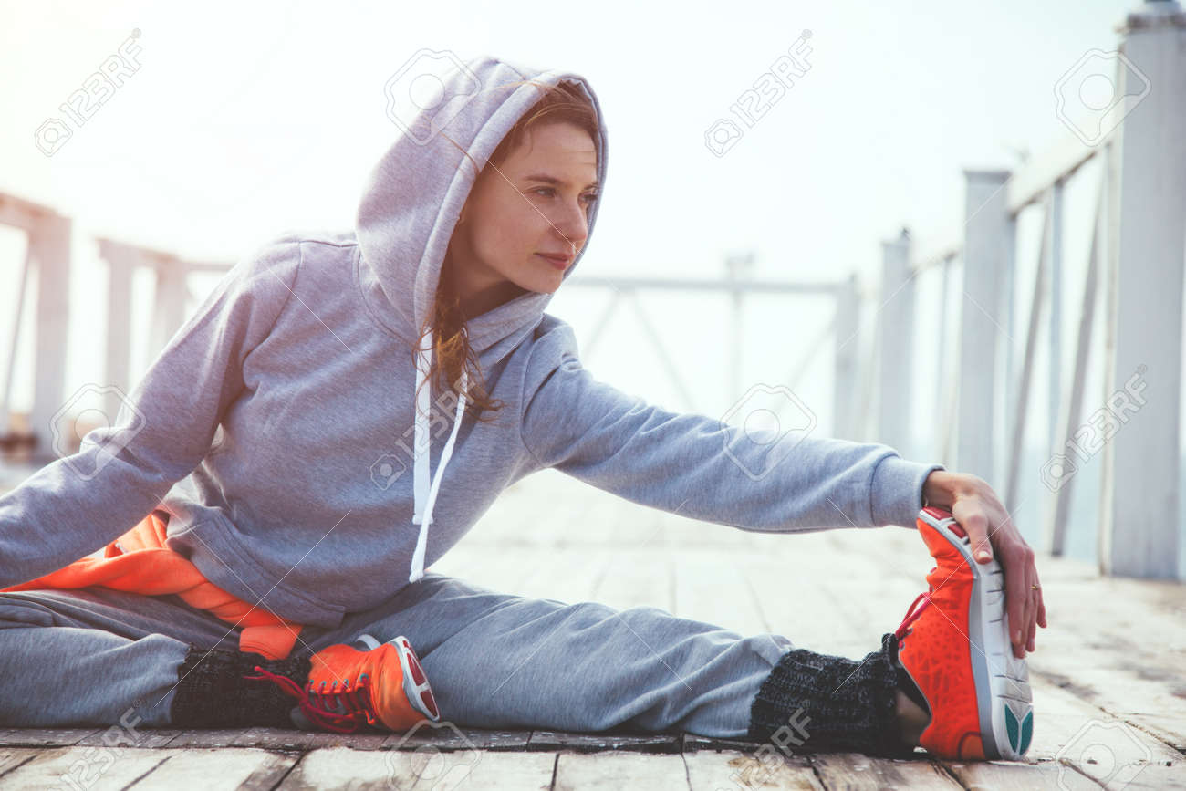 Fitness sport girl in fashion sportswear doing yoga fitness exercise in the street. Outdoor workout, urban style. - 73968688