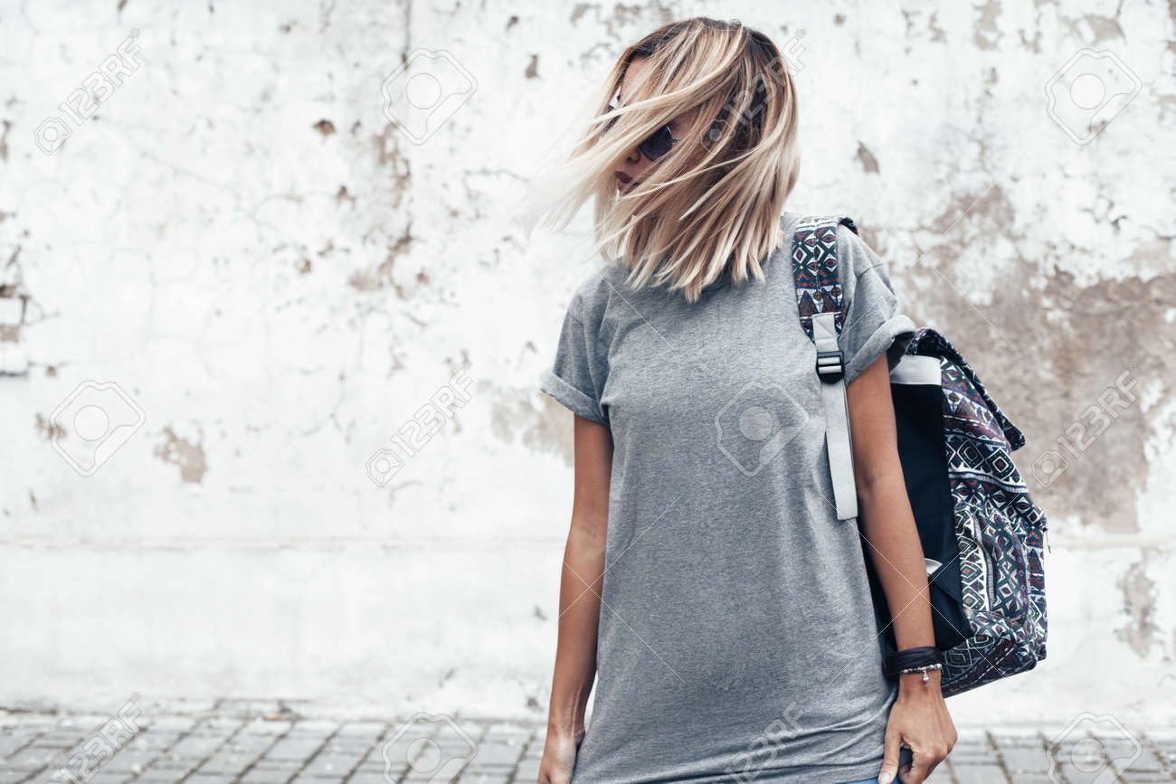Hipster girl wearing blank gray t-shirt and backpack posing against rough street wall, minimalist urban clothing style, mock up for tshirt print store - 74231834