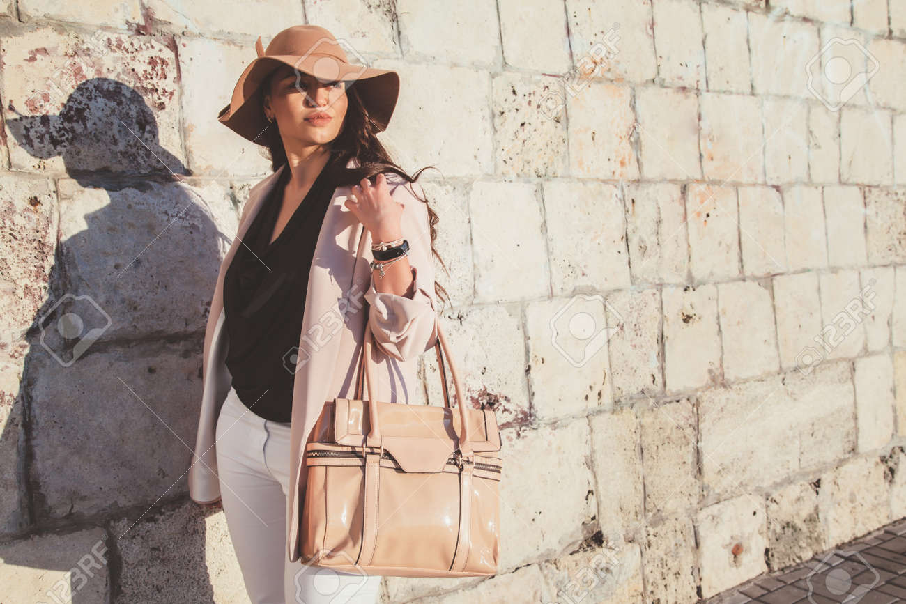Young stylish woman wearing neutral blazer, hat and handbag walking on the city street in spring. Casual fashion, elegant look. Plus size model. - 80984538