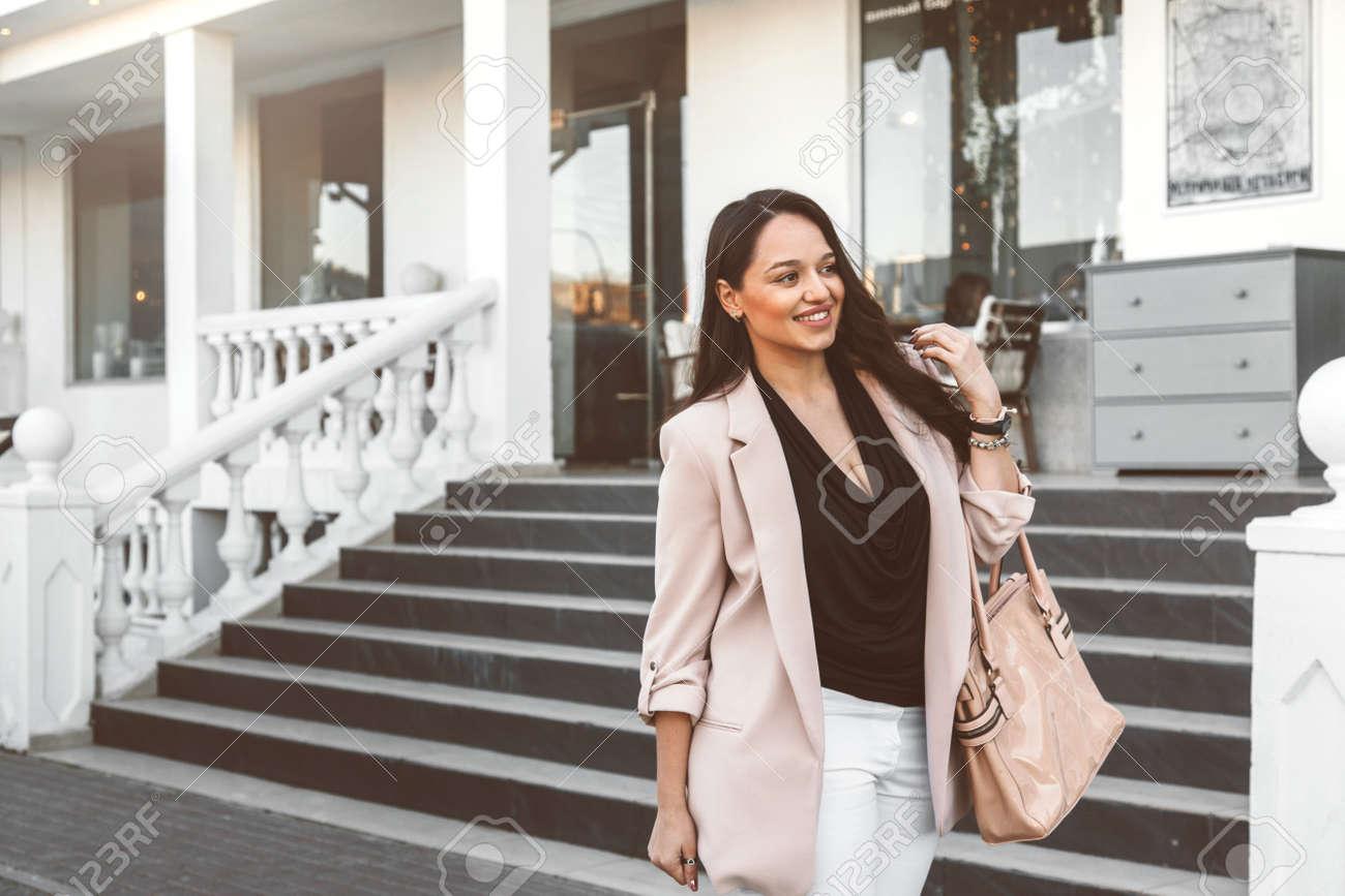 info pour 9f133 3a94e Jeune femme élégante portant un blazer neutre avec sac à main marchant sur  la rue de la ville au printemps. Mode décontracté, look élégant. Modèle de  ...