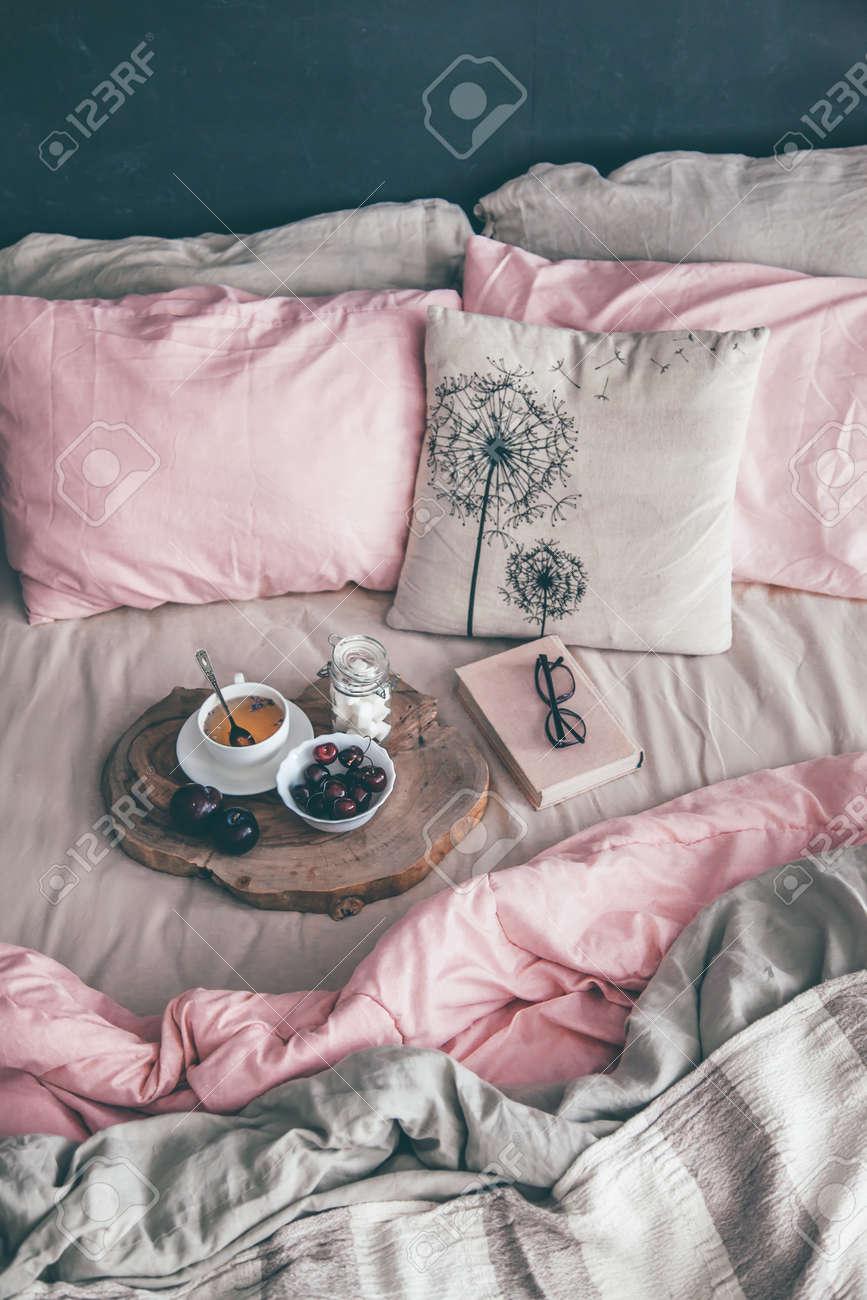 Chambre loft noire et set de literie pastel. Le lit est détruit avec le  petit-déjeuner et la lecture sur le plateau. Décoration d\'intérieur sur la  ...