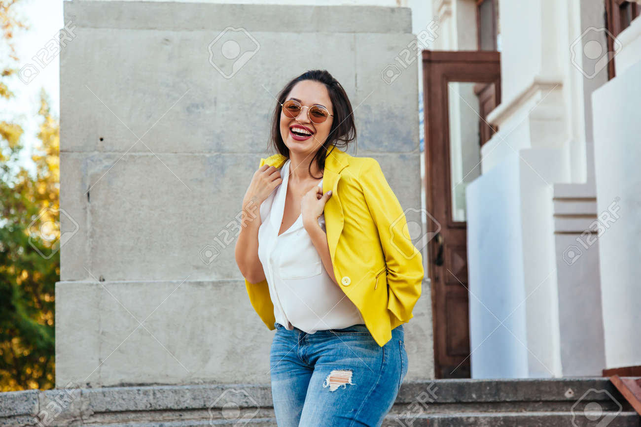 a73c00abb0e Pretty young woman wearing bright colorful jacket walking on the city street.  Casual fashion,