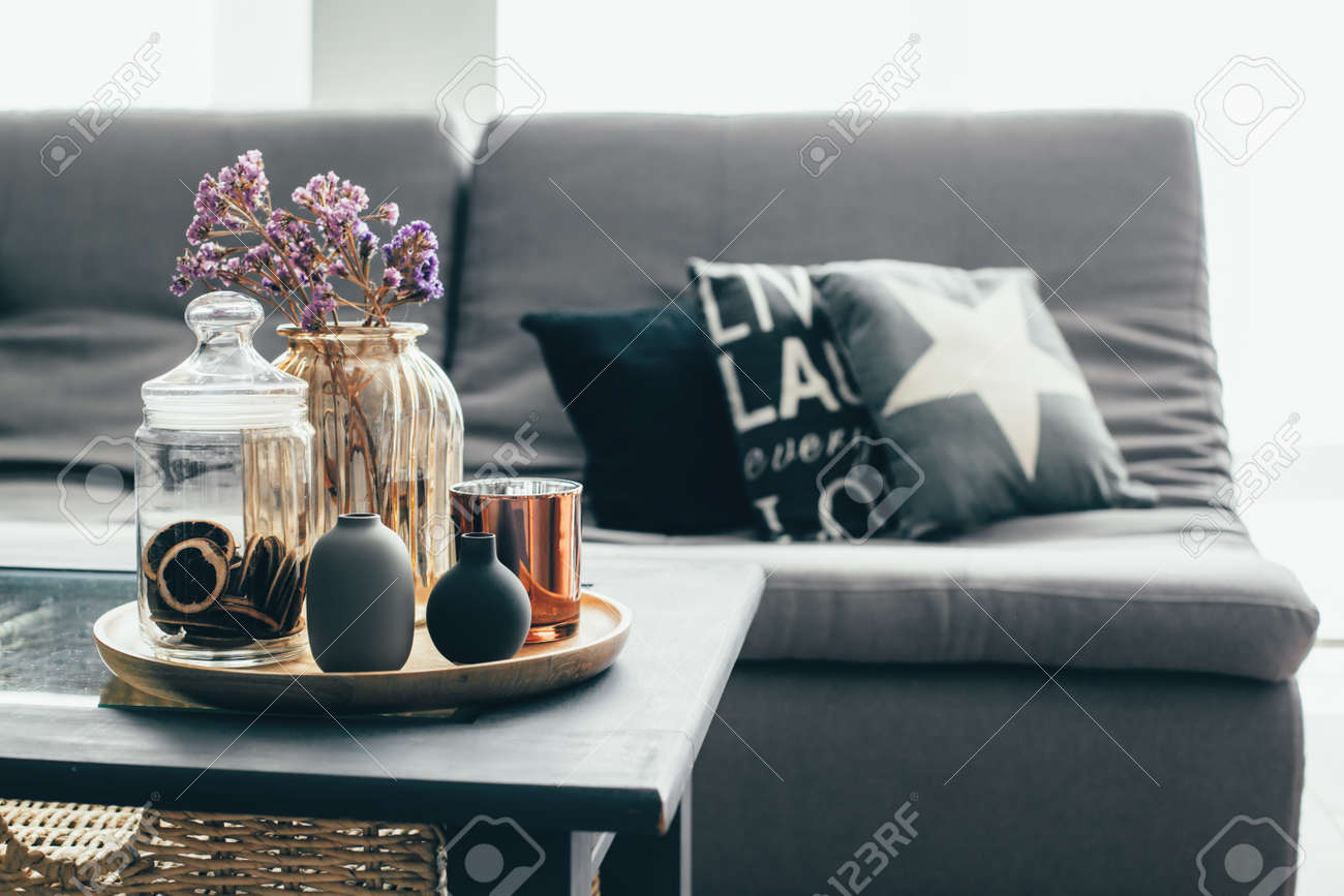 Décoration intérieure de maison dans les tons gris et marron: pot en verre  avec fleurs séchées, vase et bougie sur le plateau en bois de la table ...