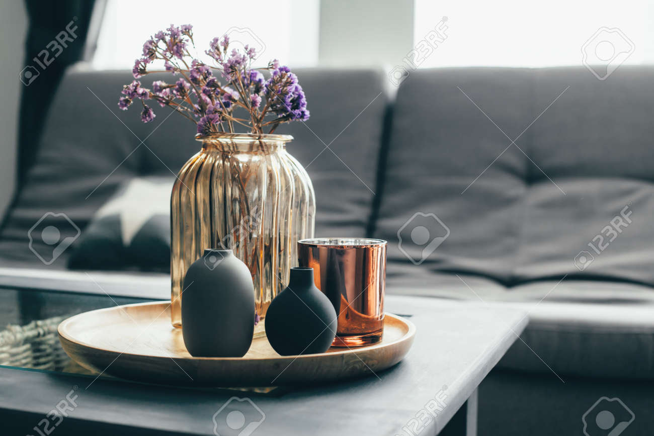 Home interior decor in gray and brown colors: glass jar with dried flowers, vase and candle on the wooden tray on the coffee table over sofa. Living room decoration. - 85971656