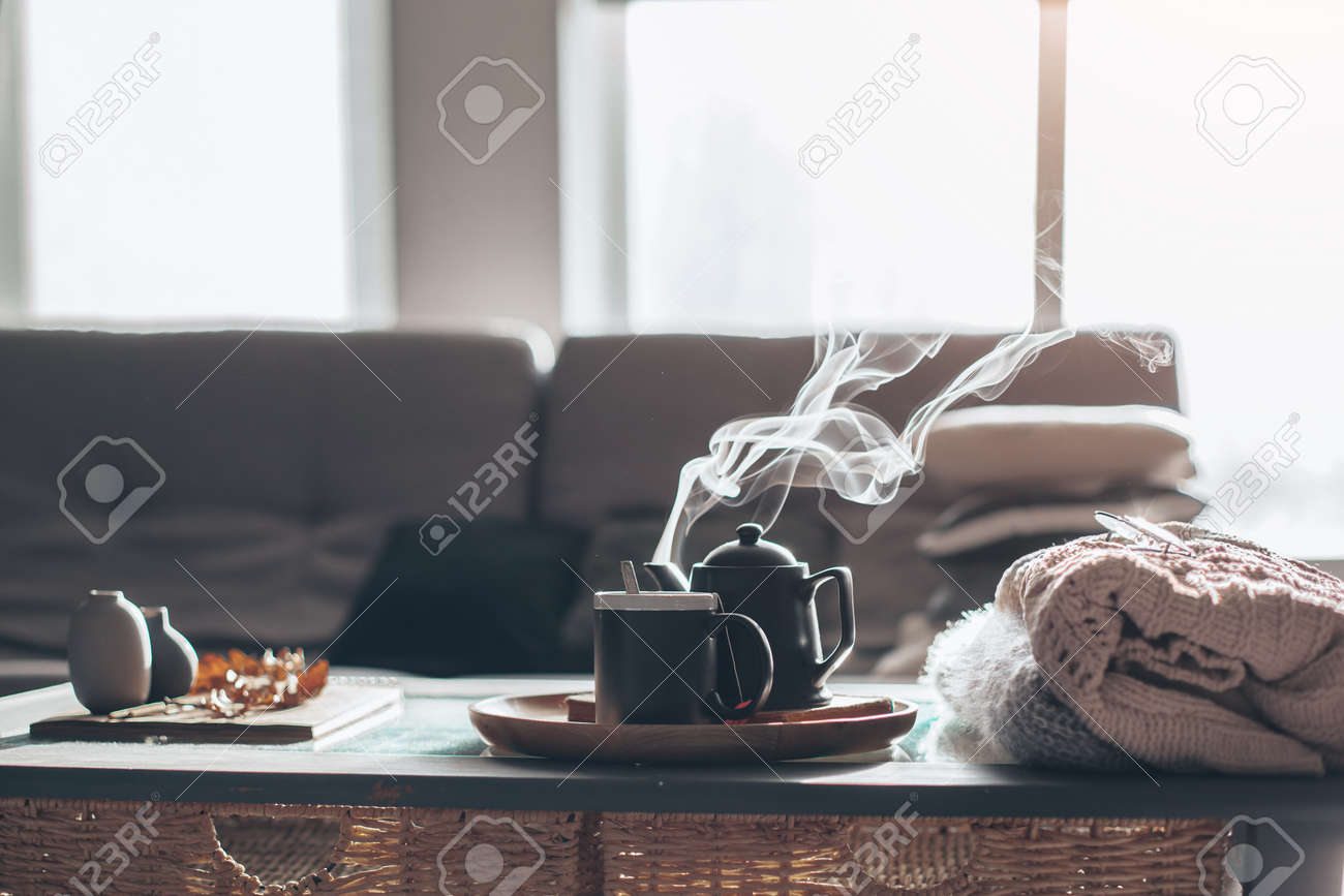 Still life details in home interior of living room. Sweaters and cup of tea with steam on a serving tray on a coffee table. Breakfast over sofa in morning sunlight. Cozy autumn or winter concept. - 85981994