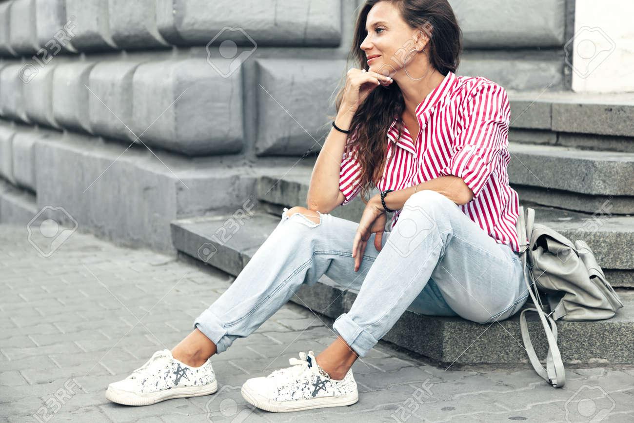 big sale performance sportswear half price Fashion model wearing ripped boyfriend jeans, red striped shirt,..