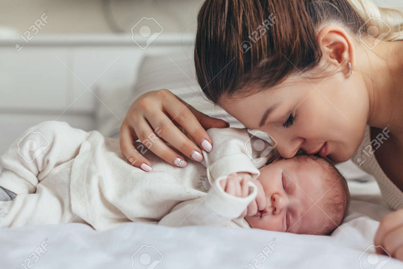 Home portrait of a newborn baby with mother on the bed mom kissing her child