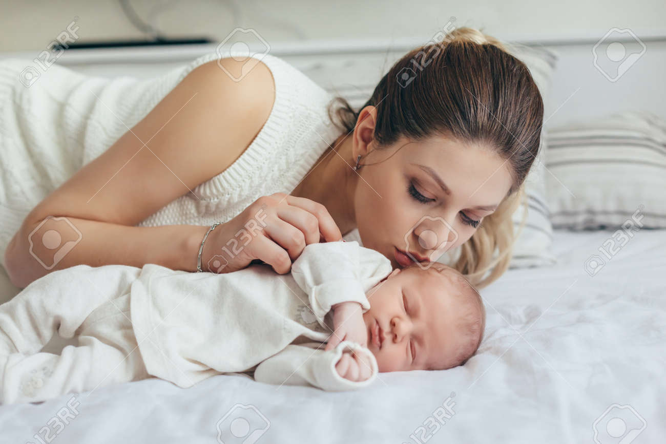 Home portrait of a newborn baby with mother on the bed mom kissing her sleeping