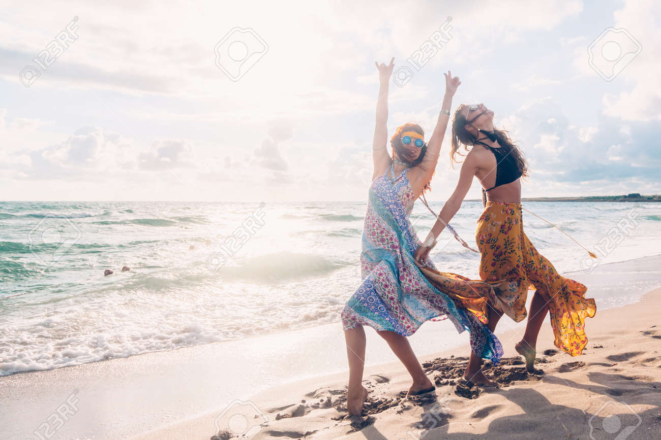 2be6a9c659 Stock Photo - Two boho friends (girls) wearing floral maxi dress and skirt  dancing on the sea shore. Bohemian clothing style.