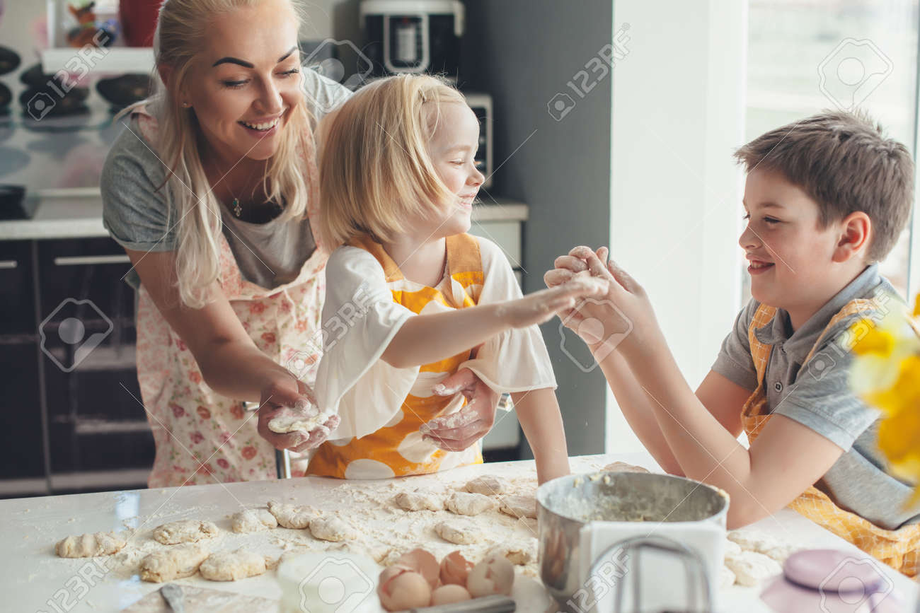 Beautiful blond mom teaching her two children cooking on the