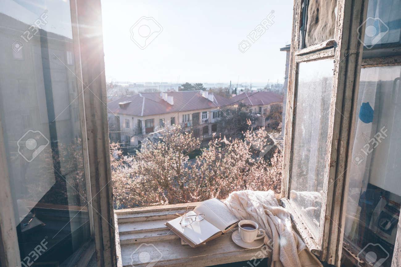 Davanzale Interno Della Finestra vecchia finestra con la vista dall'interno nell'albero di fioritura. libro  aperto, tazza di tè o caffè, occhiali e maglione lavorato a maglia sul