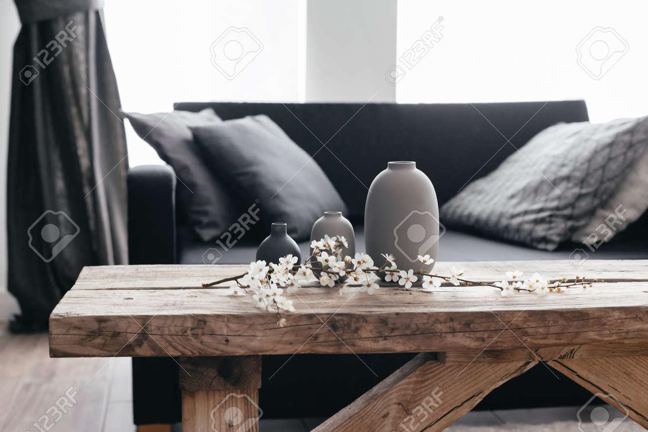 - Minimalistic Home Decor On Rustic Coffee Table Over Black Sofa