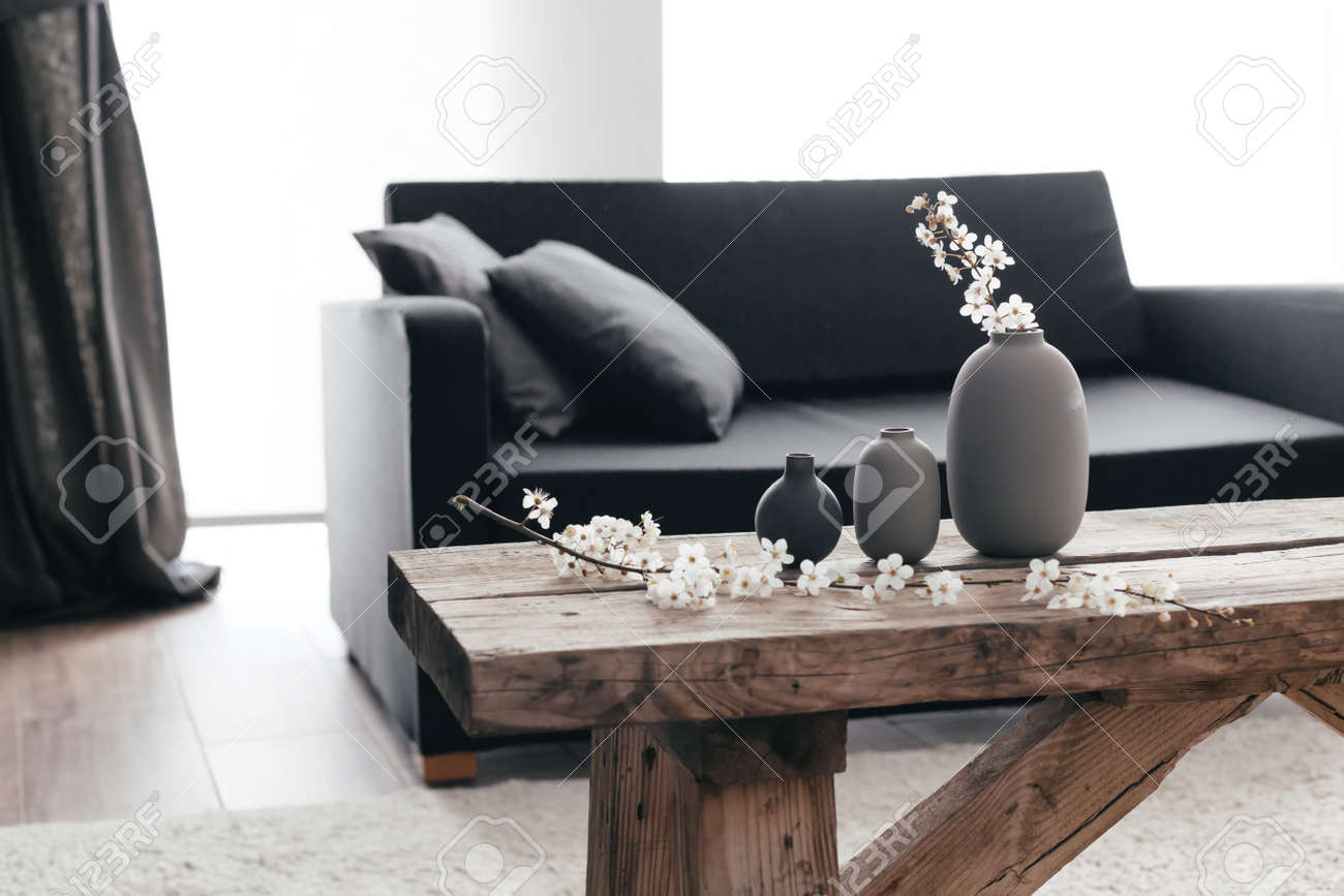Minimalistic Home Decor On Rustic Coffee Table Over Black Sofa