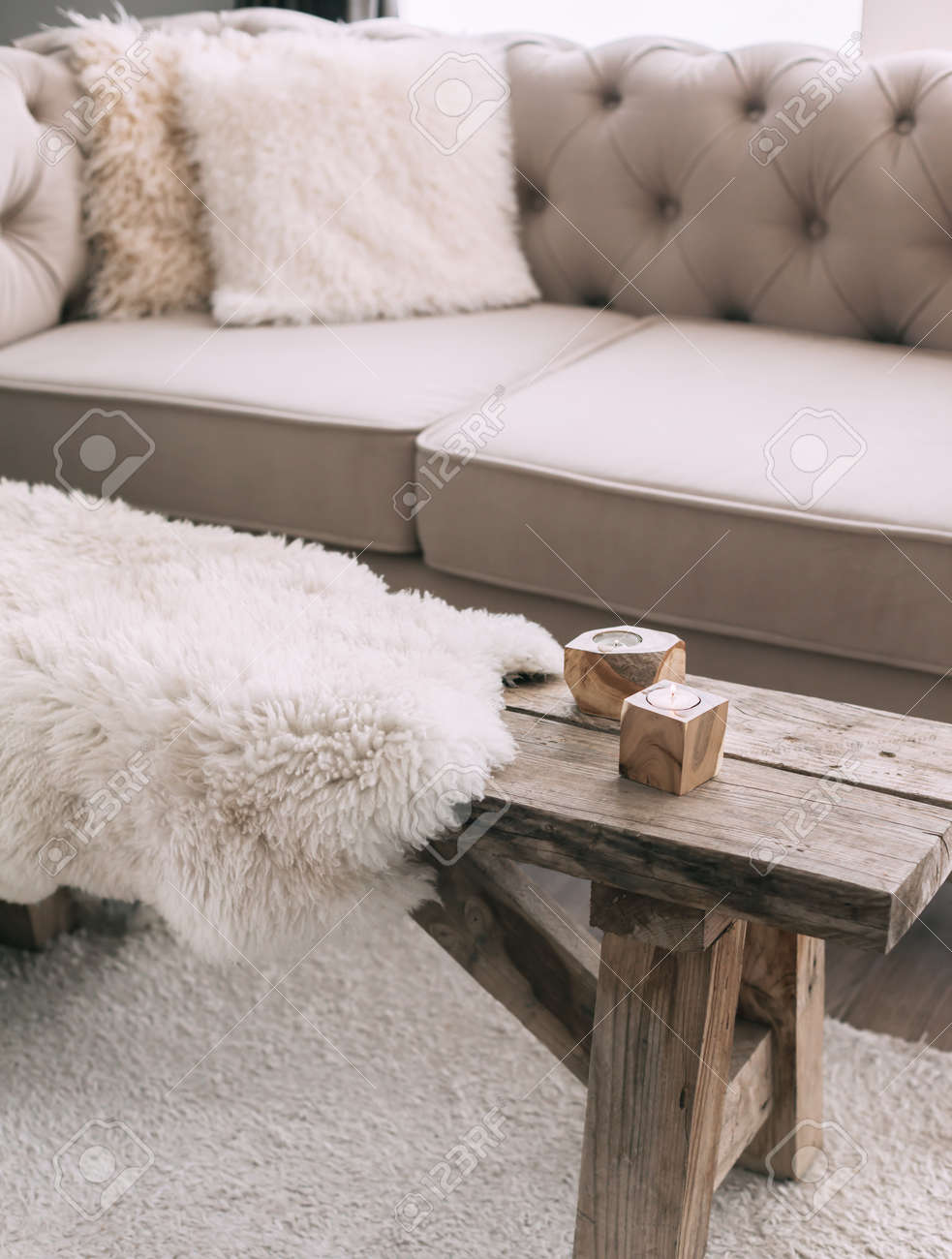 photo still life details of nordic living room sheep skin rug on rustic bench by the sofa with fur cushion
