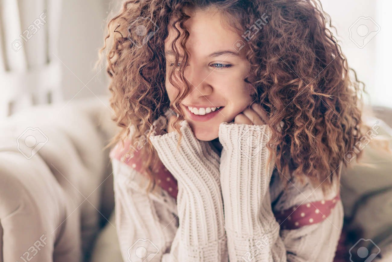 Close Up Face Portrait Of Smiling Teenage Girl With Curly Hair
