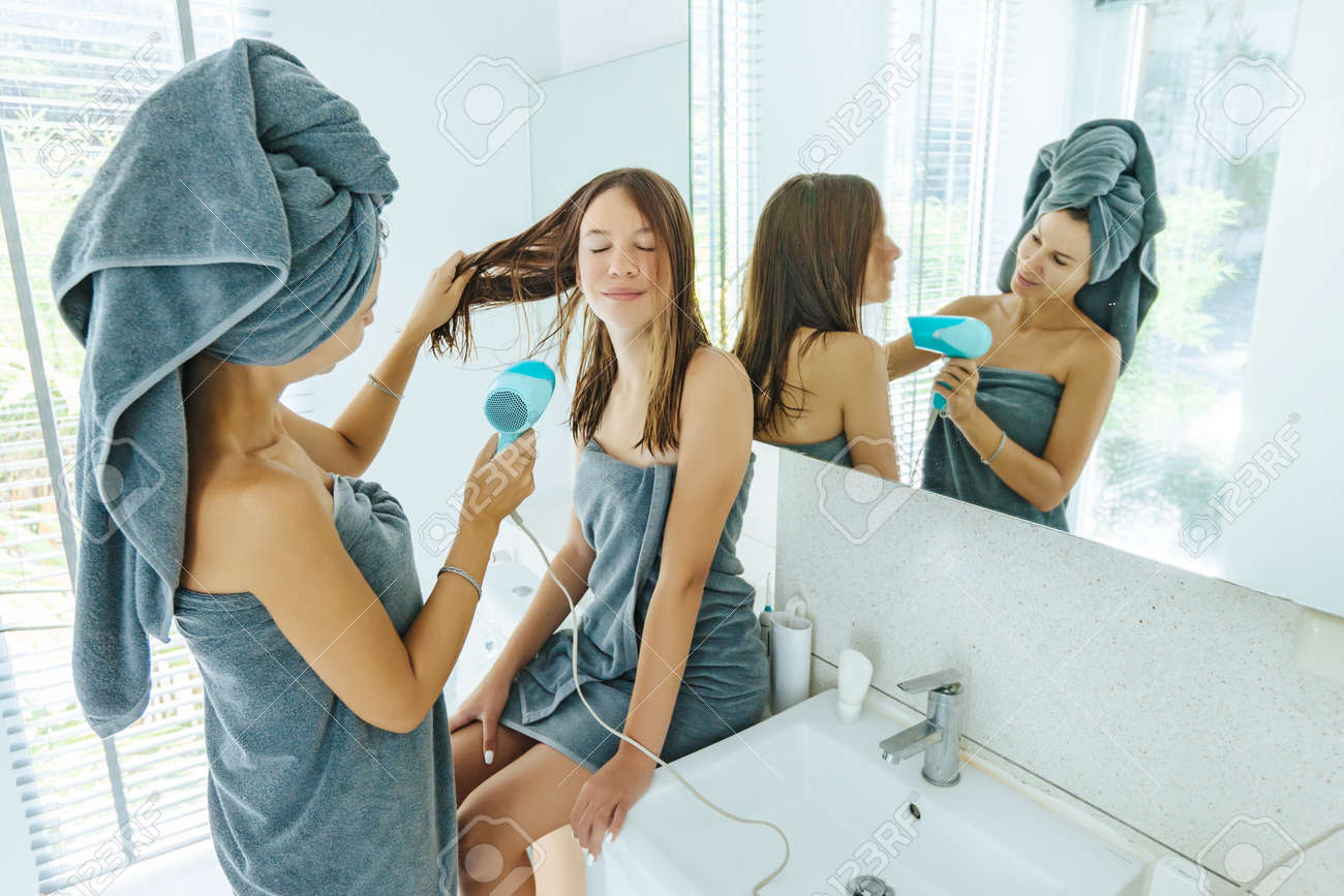 Mom with teenage dauhter making everyday routine in modern hotel bathroom together. Mother is brushing and drying child hair after shower. - 117073603