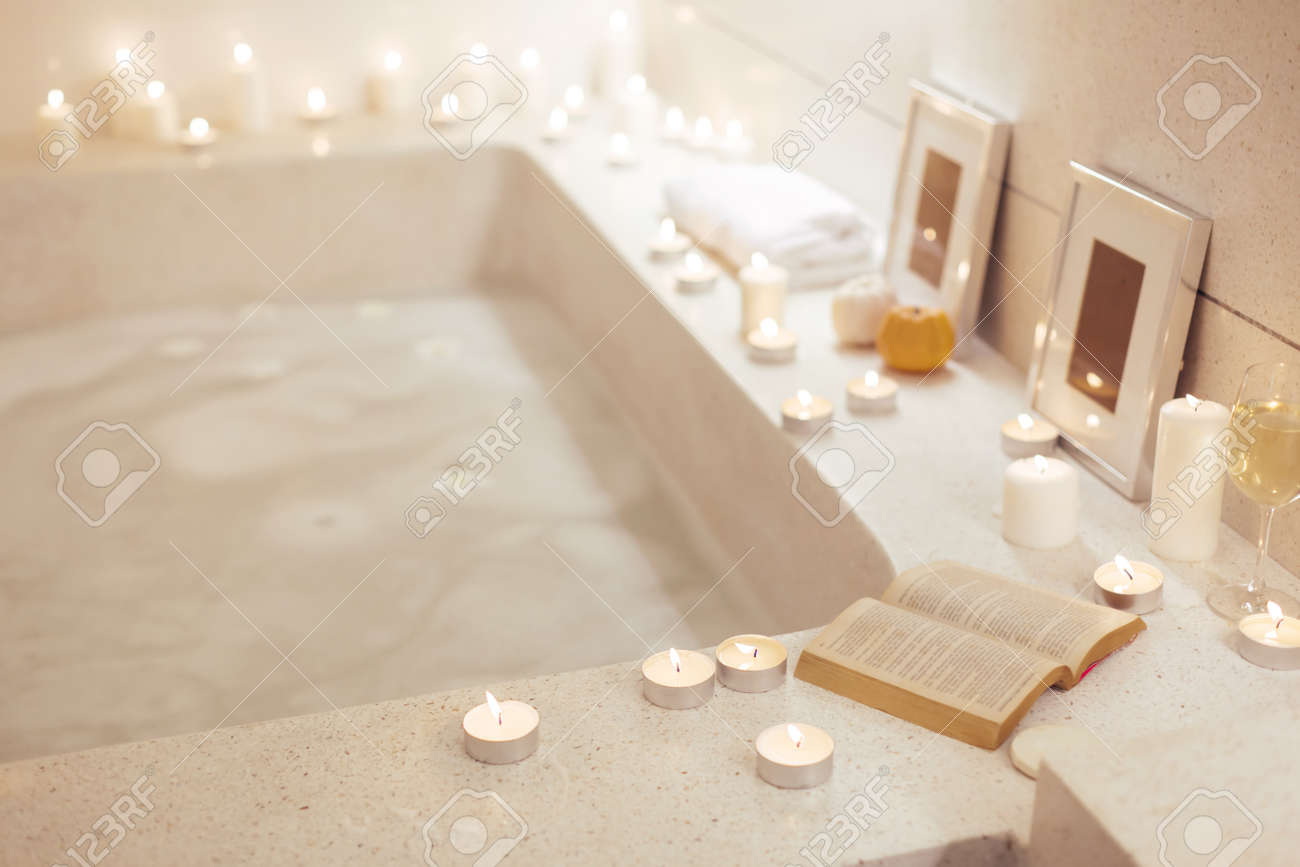 Prepared night spa bath decorated with candles,