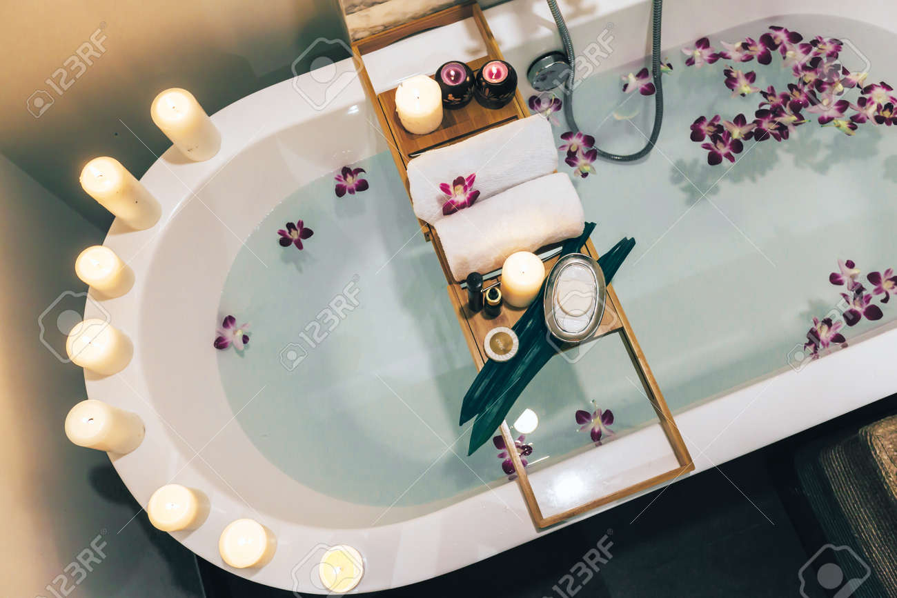 Prepared luxury spa bath decorated with flowers and candles,