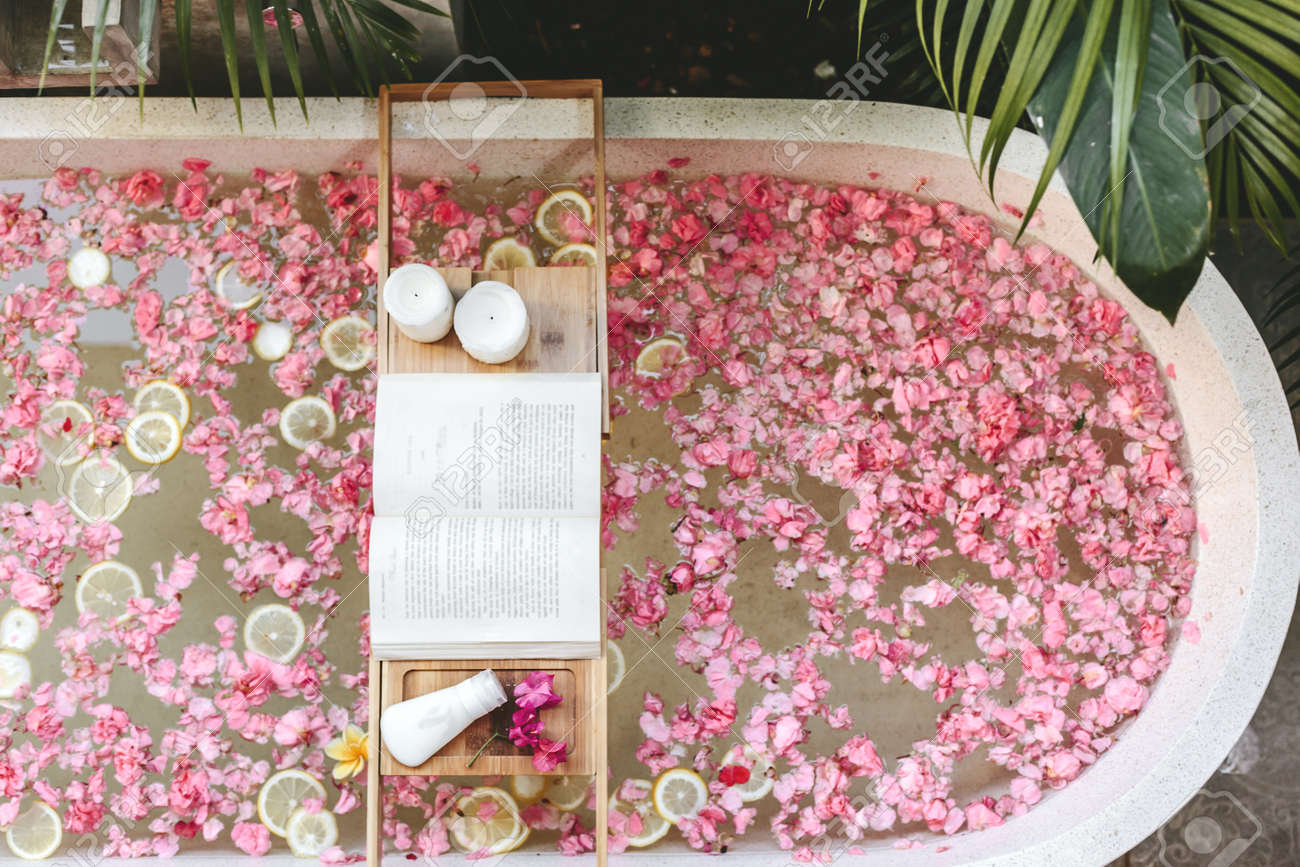 Top view of bath tub with flower petals and lemon slices  Book,