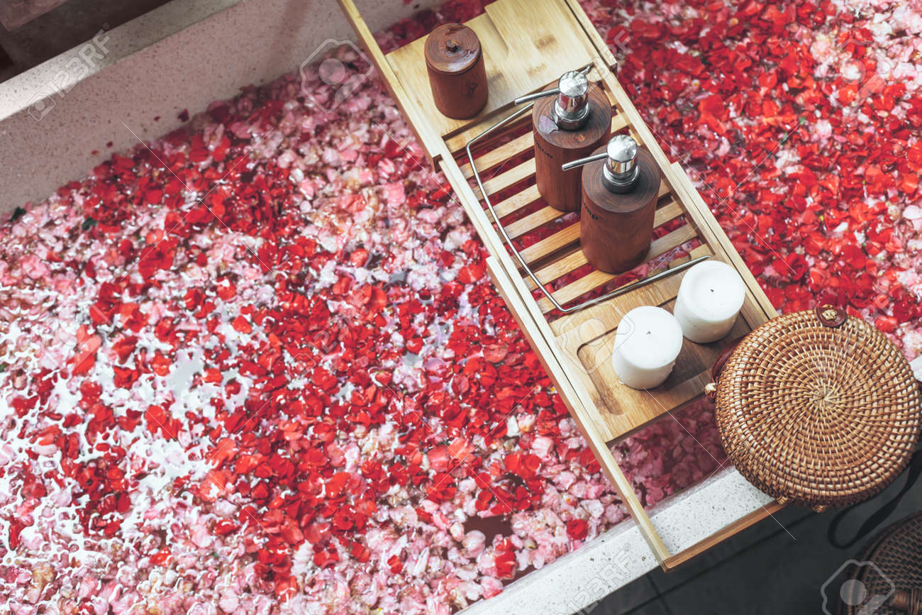 Bathtub with flower petals and beauty products on wooden tray
