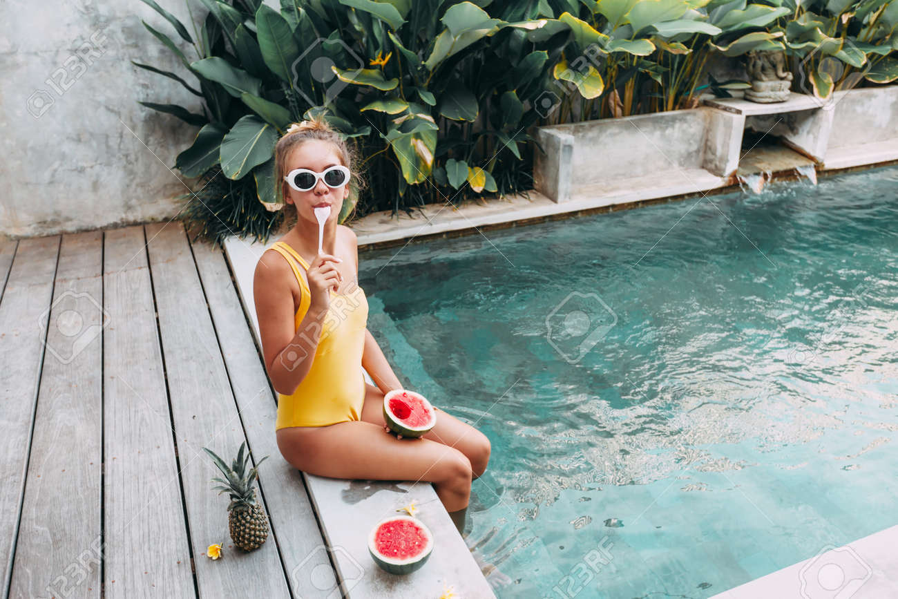 Girl relaxing and eating watermelon in the pool on luxury villa in Bali. Exotic summer diet. Tropical beach lifestyle. - 125240979