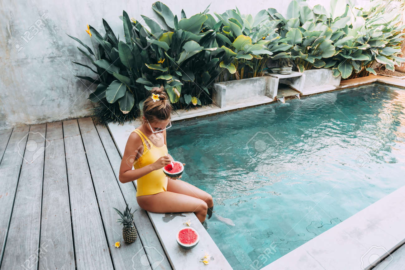 Girl relaxing and eating watermelon in the pool on luxury villa in Bali. Exotic summer diet. Tropical beach lifestyle. - 125240981