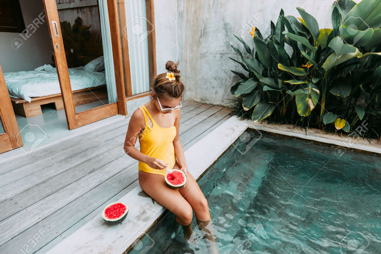 Girl relaxing and eating watermelon in the pool on luxury villa in Bali. Exotic summer diet. Tropical beach lifestyle. - 125240983