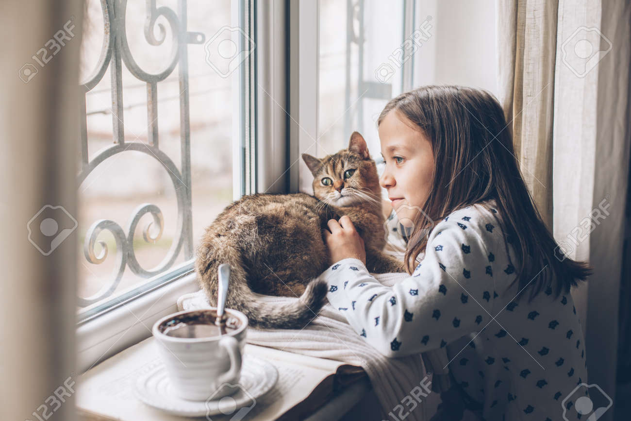 Child in pajamas relaxing on a window sill with pet. Lazy weekend with cat at home. Cozy scene, hygge concept. - 131034151