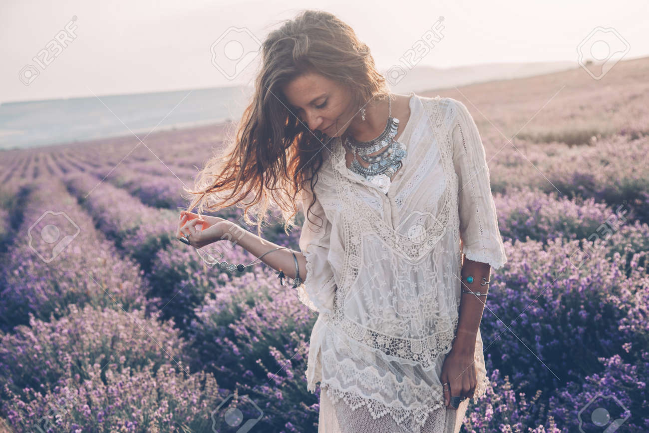 Beautiful model walking in spring or summer lavender field in sunrise sunshine. Boho style clothing and silver jewelry. - 139474997