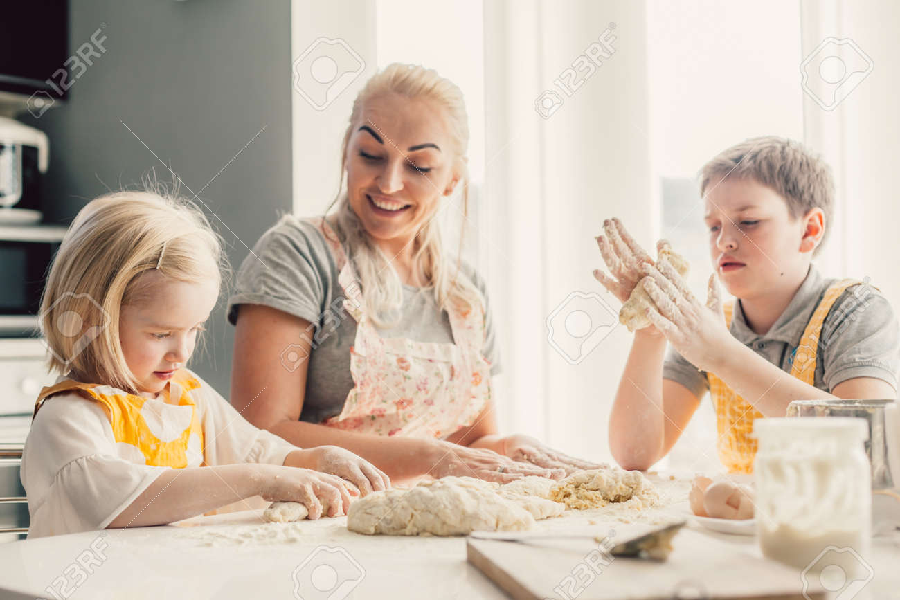Beautiful blond mom teaching her two children cooking on the kitchen. Parent making everyday breakfast together with kids. Family at home lifestyle photo. - 139464782