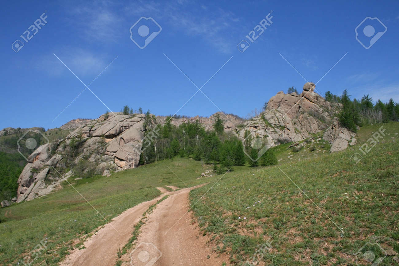 Field road leading to the mountain that looks like a seated person Stock Photo - 17419551