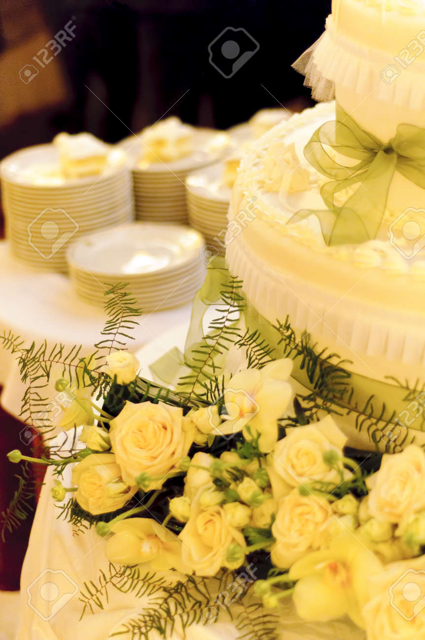 Yellow Cream Wedding Cake With Green Ribbons Decorated With Yellow ...