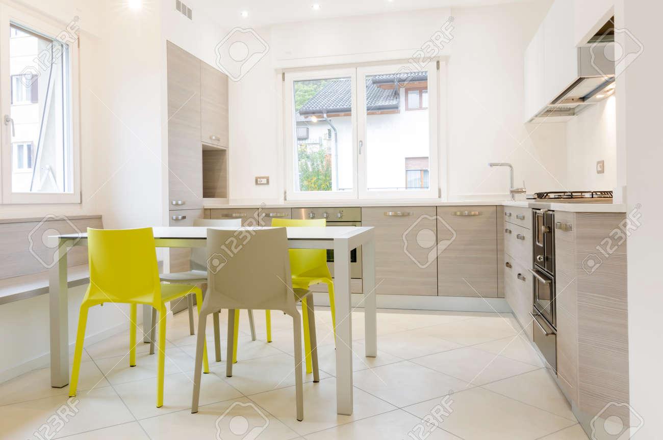 Moderne Keuken Interieur Met Houten Kasten, Witte Tafel, Grijs En ...